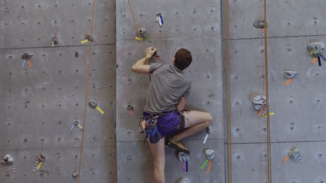 young male climbing up a rock wall - climbing wall stock videos & royalty-free footage