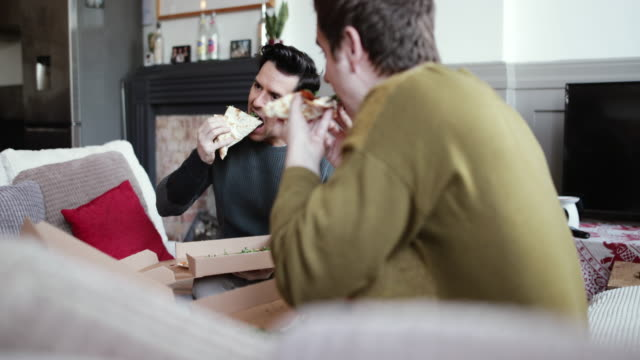 young male couple eating pizza at home - take away food stock videos and b-roll footage