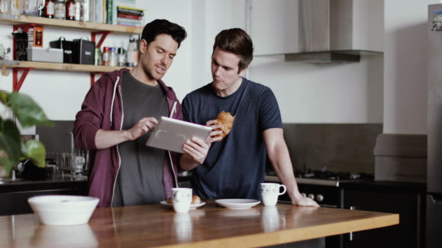 Young male couple looking at digital tablet in kitchen