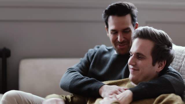 young male couple relaxing on sofa - ehemann stock-videos und b-roll-filmmaterial
