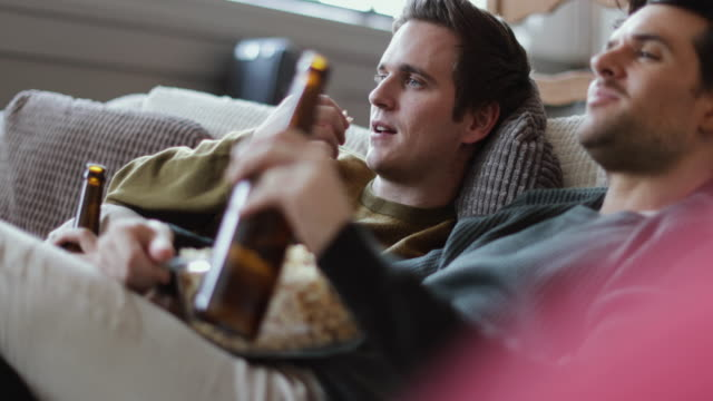 young male couple relaxing on sofa with beer and popcorn - popcorn stock-videos und b-roll-filmmaterial