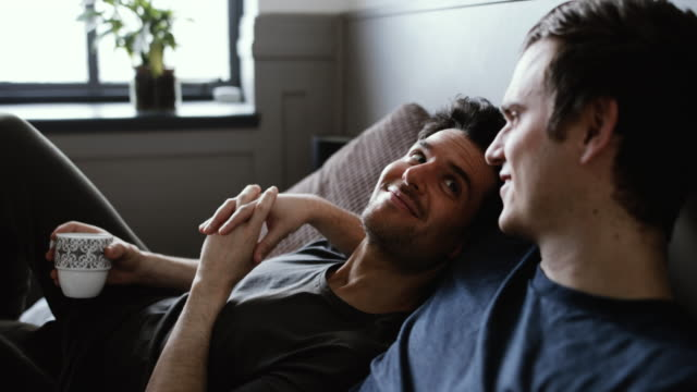 young male couple relaxing with coffee - liebe stock-videos und b-roll-filmmaterial