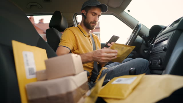 young male courier using a smartphone to locate customers while sitting in a delivery car - direction stock videos & royalty-free footage
