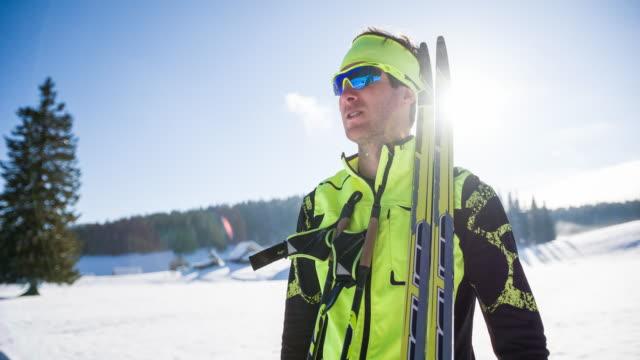 vídeos de stock e filmes b-roll de young male cross country skier getting ready - roupa de esqui
