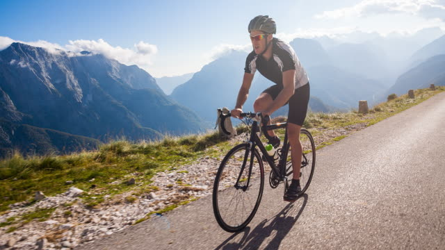 stockvideo's en b-roll-footage met young male cyclist cycling on a mountain pass - rijwiel