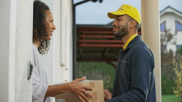young male delivery service worker delivering the package to a woman - receiving stock videos & royalty-free footage