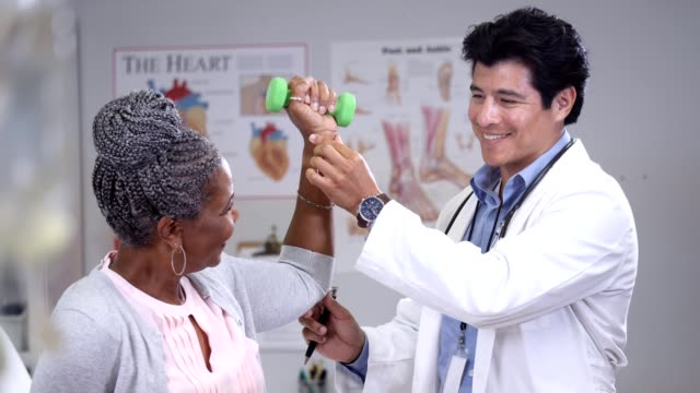 A young male doctor helps his senior female patient adjust her stretches