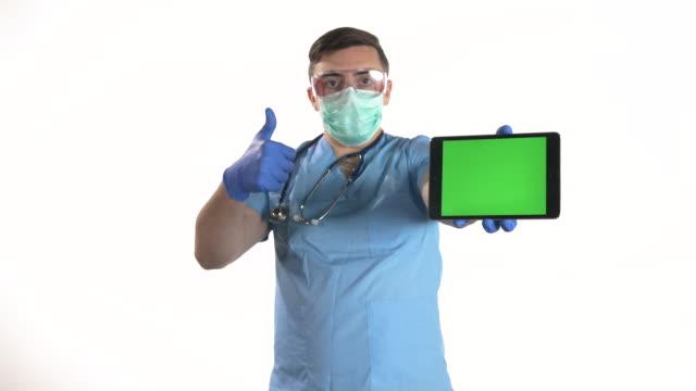 若い男性医師は親指を見せてサインを表示し、白い背景にクロマキーグリーンスクリーン付きのデジタルタブレットを保持しています - 空白の画面点の映像素材/bロール