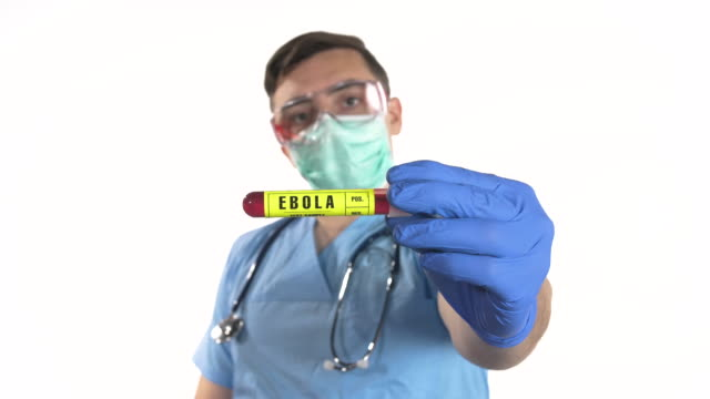 junge männliche arzt mit chirurgischen handschuhen und schutzmaske halten ebola blutprobe rohr, weißen hintergrund - schutzbrille freisteller stock-videos und b-roll-filmmaterial