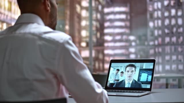 ds-junge männliche mitarbeiter bei einem videoanruf mit seinem vorgesetzten - telefonkonferenz stock-videos und b-roll-filmmaterial