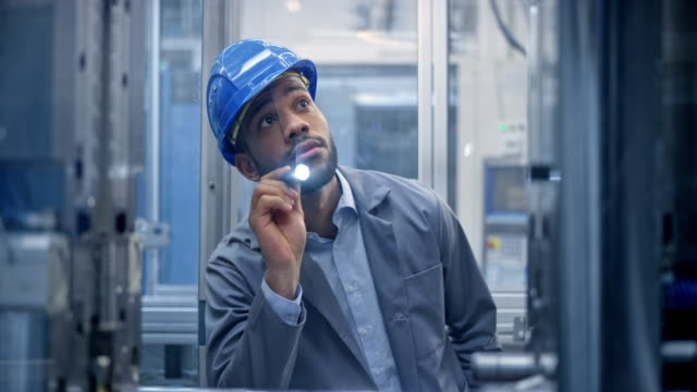 ds young male engineer inspecting the machine in the factory using a flashlight - health and safety stock videos & royalty-free footage
