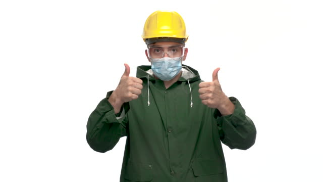 young male engineer looking at camera and show thumbs up sign, white background, slow motion - stereotypically working class stock videos & royalty-free footage