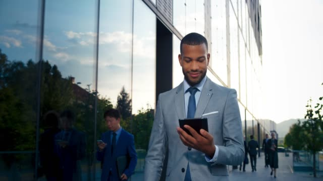 ts young male entrepreneur working on the digital tablet while walking along the modern business building - men stock videos & royalty-free footage