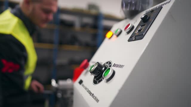 stockvideo's en b-roll-footage met jonge mannelijke fabrieksarbeider die de eindeloze riem het snijden machine begint - verwerkingsfabriek