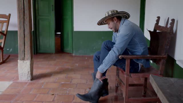 young male farmer getting ready to work changing his boots at a coffee farm - colombia stock videos & royalty-free footage