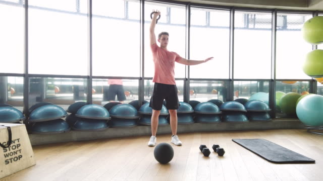 young male fitness instructor doing gym training warm up exercise with kettlebell - kettlebell stock videos & royalty-free footage