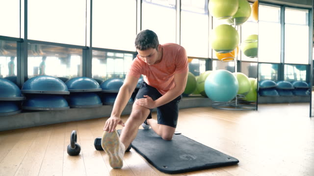 young male fitness instructor stretching legs warming up exercise - warming up stock videos & royalty-free footage