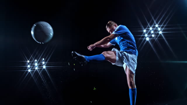 SLO MO LD Young male football player kicking the ball in the air on black background