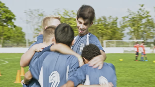 stockvideo's en b-roll-footage met jonge mannelijke voetballers in huddled omhels op gebied - tienerjongens