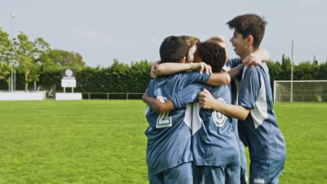 junge männliche fußballer laufen, um triumph zu feiern - sportmannschaft stock-videos und b-roll-filmmaterial