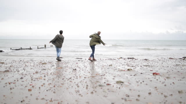 young male friends skimming stones together - kent england stock-videos und b-roll-filmmaterial