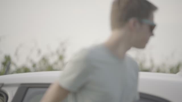 junger mann steigt aus weißen auto, kofferraum öffnet - aussteigen stock-videos und b-roll-filmmaterial