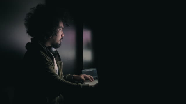 Young male hacker in hoodie sweater working on a computer in a dark room