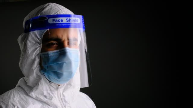 保護作業服、マスク、フェイスシールドを着用した若い男性医療従事者 - 盾点の映像素材/bロール