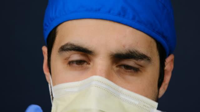 ung manlig sjukvård som arbetar med att sätta på en kirurgisk mask - slit och släng bildbanksvideor och videomaterial från bakom kulisserna