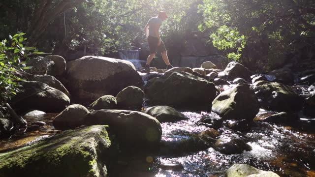 Junge männliche Wanderer, die Überquerung des Flusses