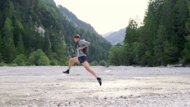 young male hiker leaping over water in summertime riverbed - jumping stock videos & royalty-free footage