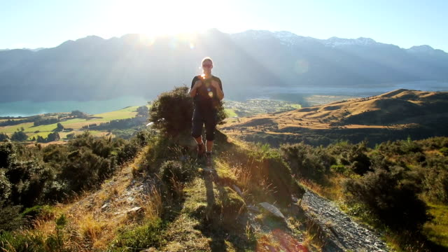 young male hiker walks onto grassy viewpoint to admire mountain view - gemeinsam gehen stock-videos und b-roll-filmmaterial