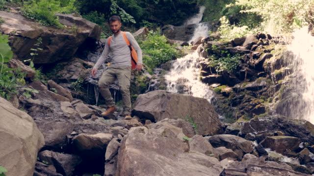 junge männchen wandern am berg wasserfall - ukraine stock-videos und b-roll-filmmaterial
