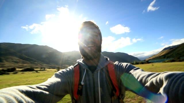 Junge männliche Wanderung dauert selfie-Porträt mit den Bergen im Hintergrund