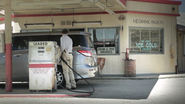 WS Young male in suit getting gas for car at gas station / Palmdale, CA, United States