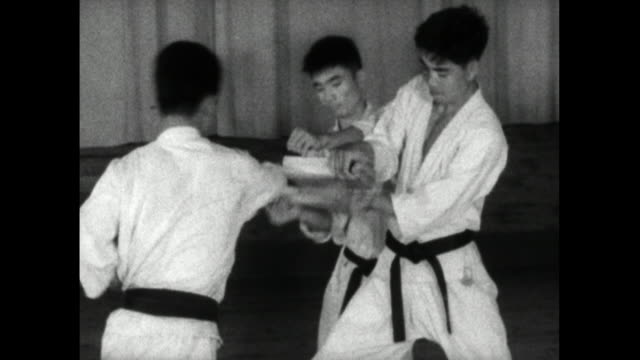 young male karate student breaks board with hand; 1959 - 1959 stock videos & royalty-free footage