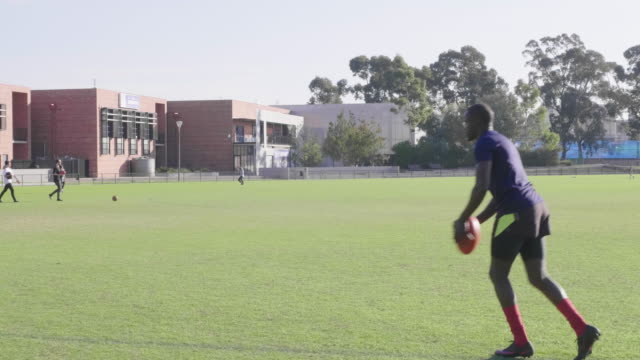 young male kicking a ball on the football pitch - kicking stock videos & royalty-free footage