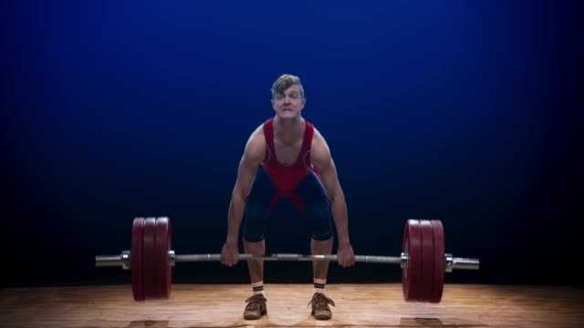 young male lifter performing the clean and jerk lift to raise the barbell above his head at a competition - weight training stock videos & royalty-free footage
