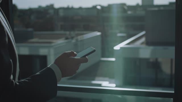 vídeos de stock, filmes e b-roll de gerente masculino novo que usa o telefone de pilha perto do indicador - só um homem
