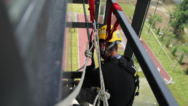 vídeos de stock e filmes b-roll de young male manual worker hanging on a climbing rope outside the building - instalar
