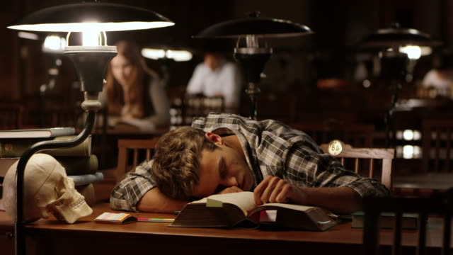DS Young male medical student falling asleep in library