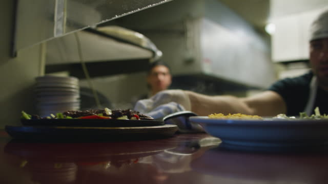 young male mexican cooks at a restaurant place steaming plates with fajitas in window and ring bell for server to pick up - mexican restaurant stock videos & royalty-free footage