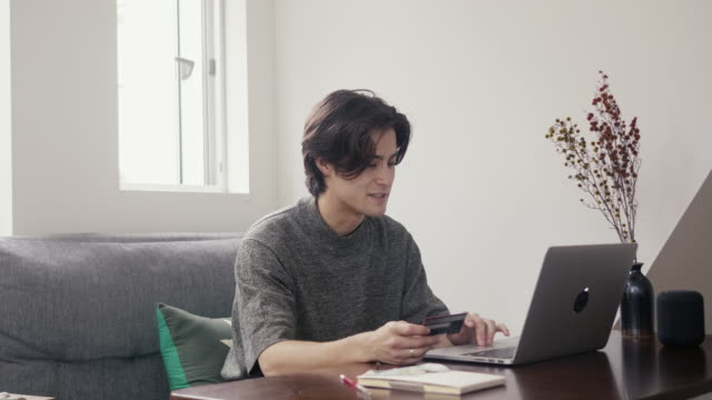 クレジットカードでオンラインで若い男性混合レース大人の買い物 - 雇用と労働点の映像素材/bロール