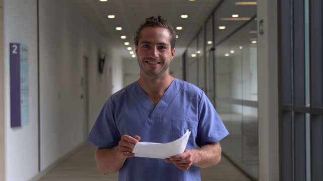 young male nurse reading some paperwork and then facing camera smiling - nurse stock videos & royalty-free footage