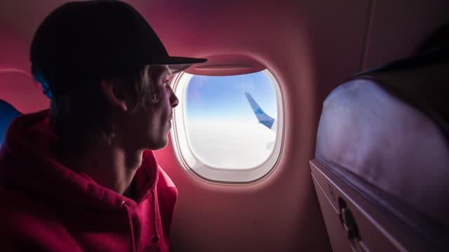 young male passenger looking through airplane window during flight - looking through an object stock videos and b-roll footage