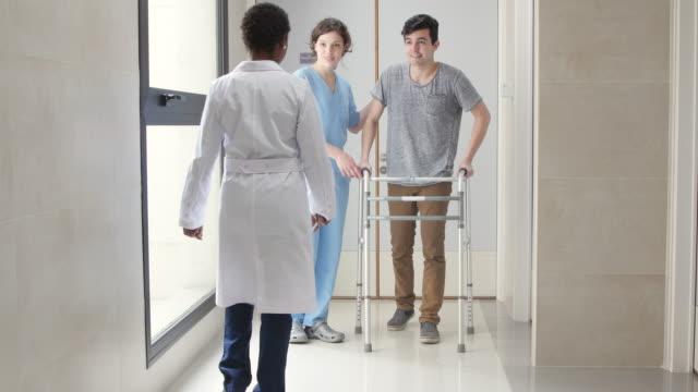 stockvideo's en b-roll-footage met jonge mannelijke patiënt met behulp van een wandelaar met verpleegkundige naast hem lopen - tegenspoed