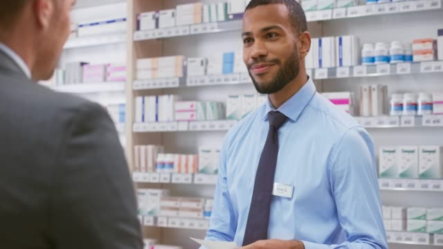 young male pharmacist being handed a prescription by a male business man - males stock videos & royalty-free footage