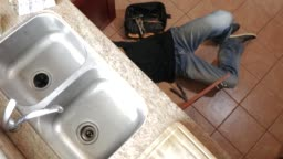 Young male plumber sitting on the floor and replacing the trap pipe under a bathroom sink