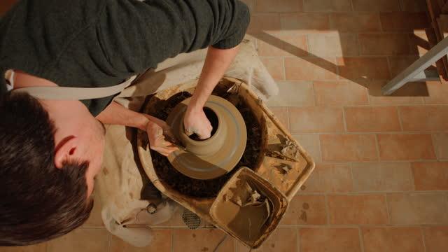vidéos et rushes de cs jeune potier mâle soulevant les murs de l'argile tournant sur la roue - poterie