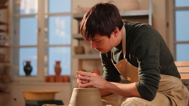 陶芸家の車輪の鍋の底をトリミング若い男性の陶芸家 - 陶芸家点の映像素材/bロール